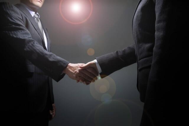 ビジネスで業務提携をして握手をするビジネスマン