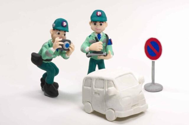 駐車監視員(緑の爺)が駐車違反の取り締まりをしている様子
