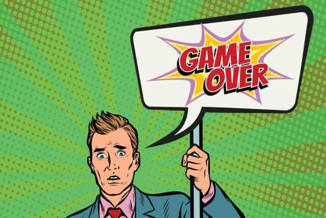 ゲームオーバーのポスターを掲げるサラリーマン