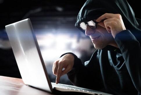 パソコンでスパムメールを送ろうとしているハッカー