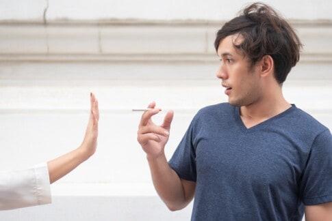 女性の手が男性を止めて喫煙しないようにする。禁煙