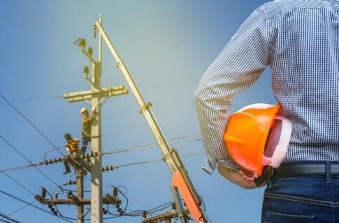 クレーンを使って電柱で作業をしている電気技師