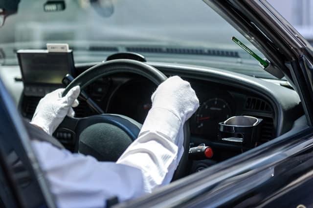 ハンドルを握るタクシー運転手