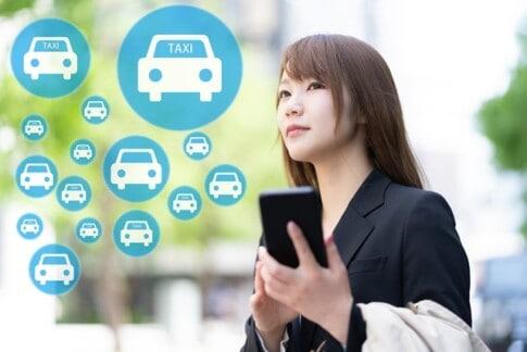 配車アプリを使ってタクシーを呼ぶ女性