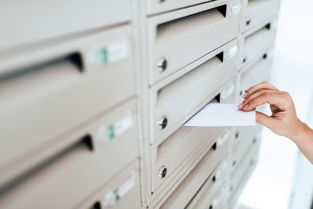 郵便ポストに不在票を入れる配達員