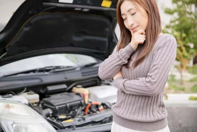 バッテリーが上がって苦慮する女性ドライバー