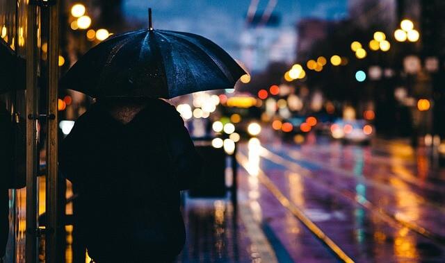 雨が降っているのに荷物を待つ女性