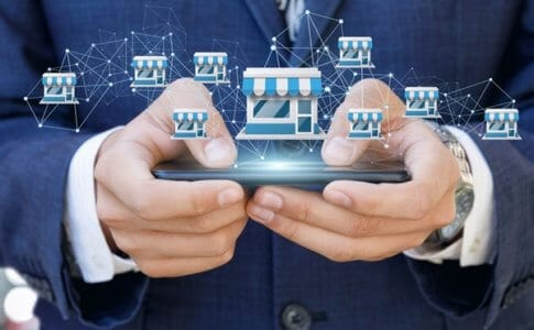 モバイルでフランチャイズシステムを示すビジネスマン。
