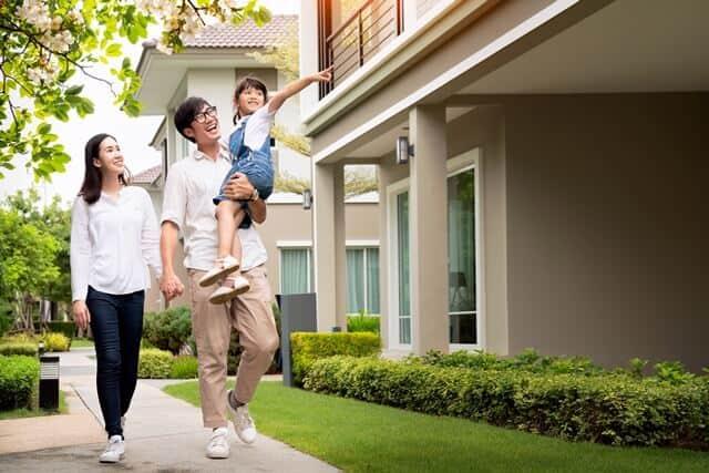 彼らの新しい家の外で笑っている美しい家族の肖像画