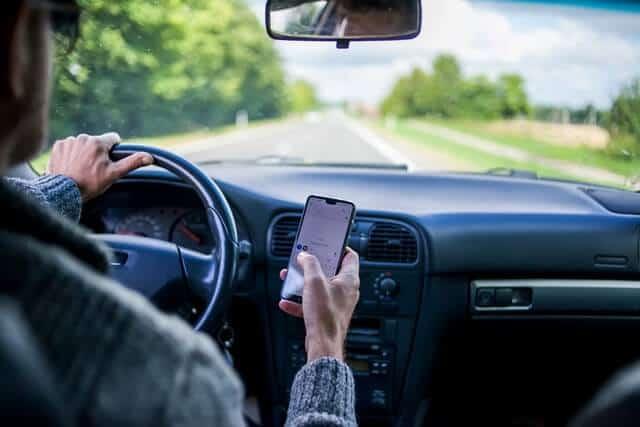 車の運転中にスマートフォンを使う男性。 運転中の危険な行為