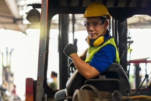 フォークリフトを運転し、工場で親指を立てる男性従業員